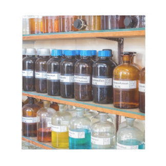 Rows of fluid chemicals in bottles at chemistry notepad