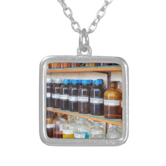 Rows of fluid chemicals in bottles at chemistry silver plated necklace