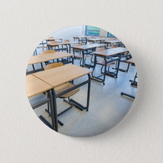 Rows of tables and chairs in classroom 2 inch round button