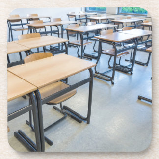 Rows of tables and chairs in classroom coaster