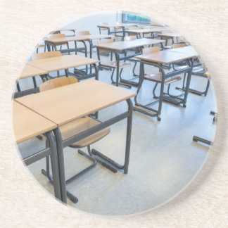 Rows of tables and chairs in classroom drink coaster