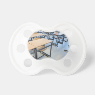 Rows of tables and chairs in classroom pacifier