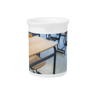 Rows of tables and chairs in classroom pitcher