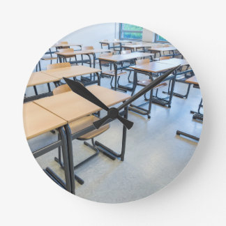 Rows of tables and chairs in classroom wallclock