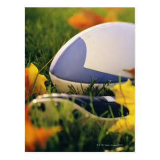 Rugby ball and shoe on lawn in autumn postcard
