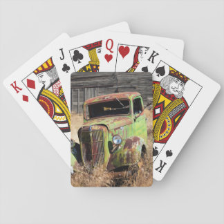 Rusting car in front of abandoned farm poker deck