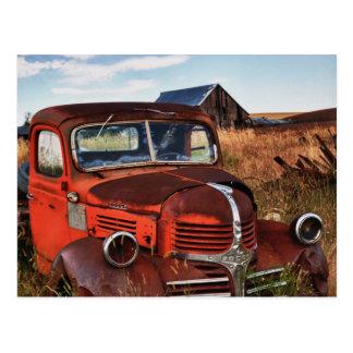 Rusting orange Dodge truck with abandoned farm Postcard