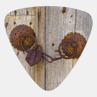 Rusty vintage old iron padlock on a wooden door , guitar pick
