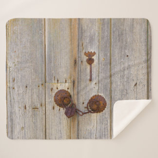 Rusty vintage old iron padlock on a wooden door .. sherpa blanket