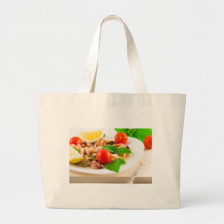 Salad of blanched pieces of seafood on a plate large tote bag
