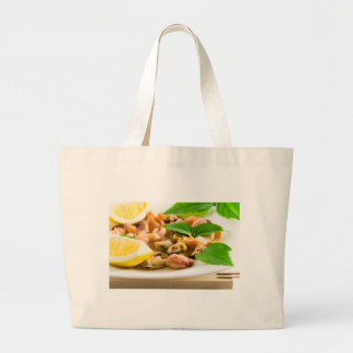 Salad of blanched seafood on a white plate large tote bag