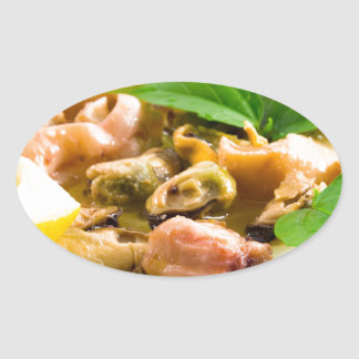 Salad of blanched seafood on a white plate oval sticker