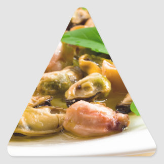 Salad of blanched seafood on a white plate triangle sticker