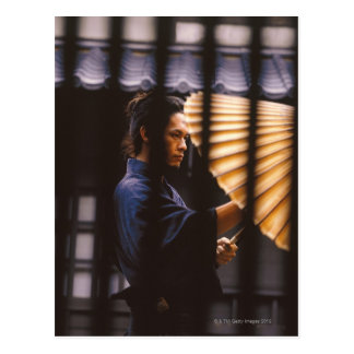 Samurai warrior keeping an umbrella postcard
