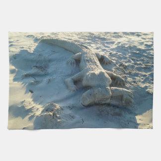 Sand art alligator holding human arm. kitchen towel