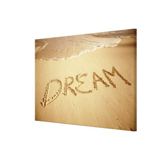 Sand writing 'Dream' with incoming surf at top Canvas Prints
