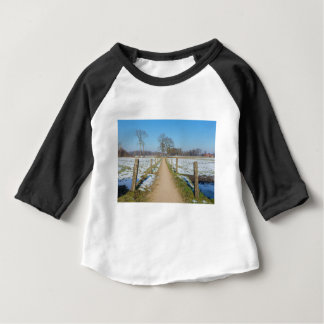 Sandpath between snowy meadows in dutch winter baby T-Shirt