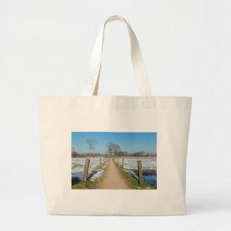 Sandpath between snowy meadows in dutch winter large tote bag