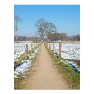 Sandpath between snowy meadows in dutch winter letterhead