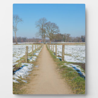 Sandpath between snowy meadows in dutch winter plaque