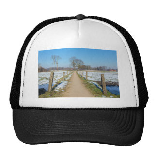 Sandpath between snowy meadows in dutch winter trucker hat