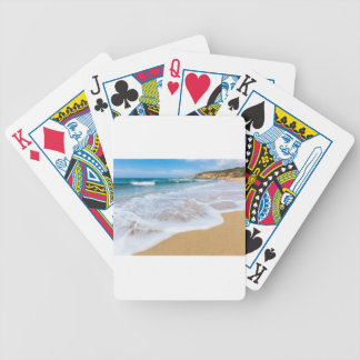 Sandy beach sea waves and mountain at coast bicycle playing cards