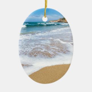 Sandy beach sea waves and mountain at coast ceramic oval ornament