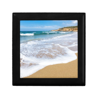 Sandy beach sea waves and mountain at coast gift box