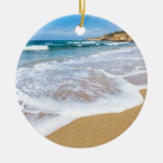 Sandy beach sea waves and mountain at coast round ceramic ornament