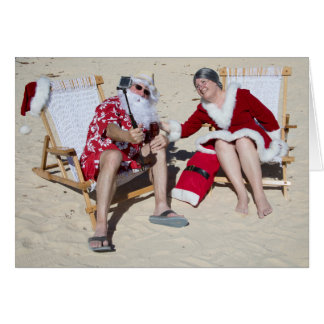 Santa and Mrs Claus taking selfie on beach Card
