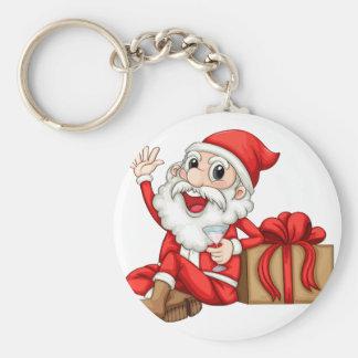 Santa sitting beside a gift basic round button keychain