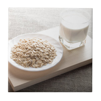 Saucer of cereal and a glass of milk in the backli tiles