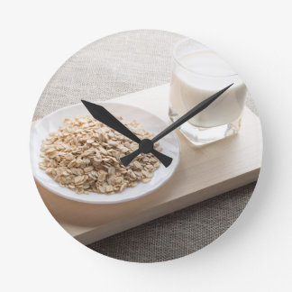 Saucer of cereal and a glass of milk in the backli wall clock