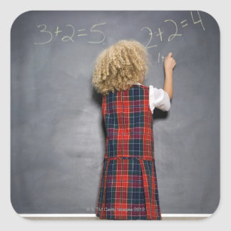 School girl (6-7) writing on blackboard, square sticker