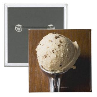 Scoop of ice cream in ice cream scoop (overhead pins