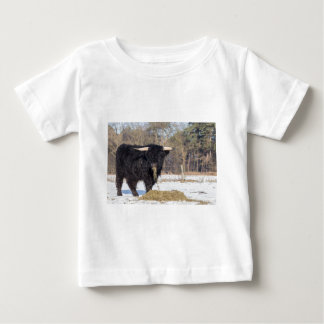 Scottish highlander bull eating hay in winter snow baby T-Shirt