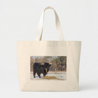 Scottish highlander bull eating hay in winter snow large tote bag