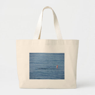 Sea diver in scuba suit swim in water large tote bag