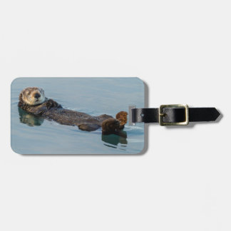 Sea otter floating on back in ocean luggage tag