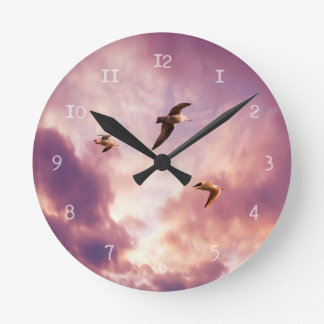 Seagulls flying in a sunset sky round clock