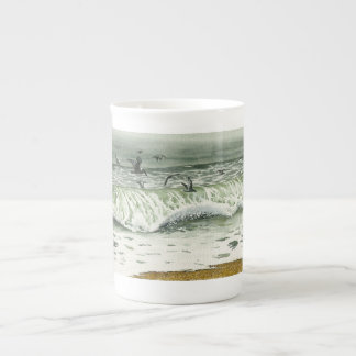 Seascape with pelicans flying over the waves tea cup