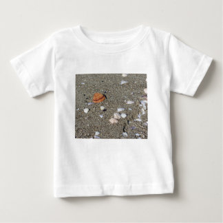 Seashells on sand. Summer beach background Baby T-Shirt