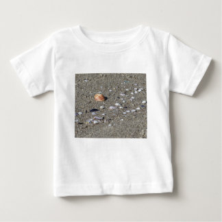 Seashells on sand. Summer beach background Baby T-Shirt