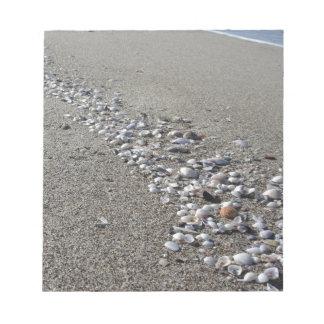 Seashells on sand. Summer beach background Notepad