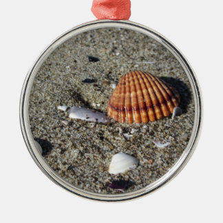 Seashells on sand Summer beach background Top view Metal Ornament