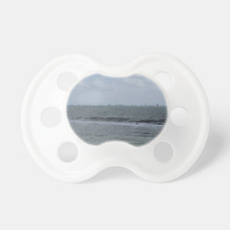 Seashore of beach with sailboats on the horizon baby pacifiers