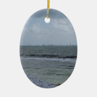 Seashore of beach with sailboats on the horizon ceramic oval ornament