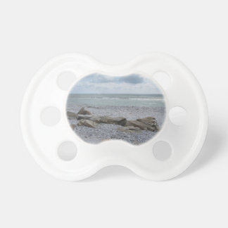 Seashore of beach with sailboats on the horizon pacifier