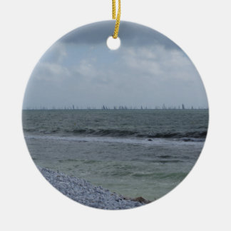 Seashore of beach with sailboats on the horizon round ceramic ornament