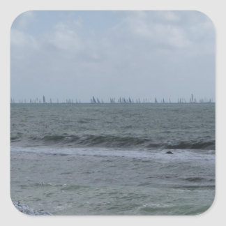 Seashore of beach with sailboats on the horizon square sticker